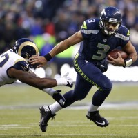 Seattle Seahawks quarterback Russell Wilson (3) pushes past St. Louis Rams' Eugene Sims for a 15-yard run in the second half of an NFL football game, Sunday, Dec. 30, 2012, in Seattle. The Seahawks won 20-13. (AP Photo/Elaine Thompson)
